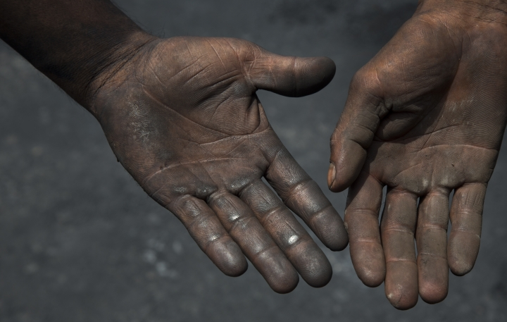 """In this July 14, 2017 photo, contractual laborers who sweep and collect petroleum coke for transport to factories display their hands in Rampur, about about 210 kilometers (130 miles) from New Delhi, India. Petroleum coke, the bottom-of-the-barrel leftover from refining Canadian tar sands crude and other heavy oils, is cheaper and burns hotter than coal. But it also contains more planet-warming carbon and far more heart- and lung-damaging sulfur - a key reason few American companies use it. Refineries instead are sending it around the world, especially to energy-hungry India, which last year got almost a fourth of all the fuel-grade """"petcoke"""" the U.S. shipped out, an Associated Press investigation found. (AP Photo/Vaishnavee Sharma)"""