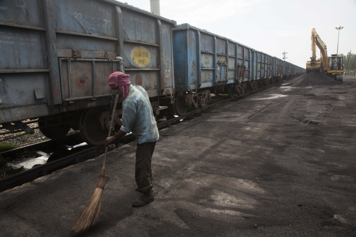 In this July 14, 2017 photo, Baburam sweeps domestically produced petroleum coke to be transported onto trucks hired by local factories in Rampur about 210 kilometers (130 miles) from New Delhi, India. The petcoke being burned in countless factories and plants is contributing to dangerously filthy air in India, which already has many of the world's most polluted cities. India's energy-hungry industries like petcoke because it's cheaper and burns hotter than coal; they also defend their use by saying they're recycling a waste that's being produced anyway. (AP Photo/Vaishnavee Sharma)